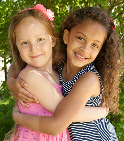 Two young girls hugging each other and smiling while posing for a picture.