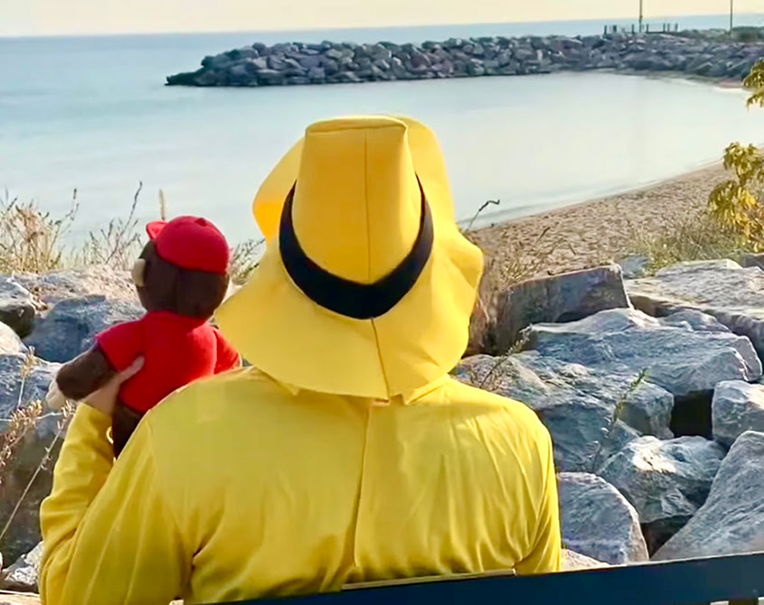 The Man in the Yellow Hat looks out over the lakefront with his friend Curious George.