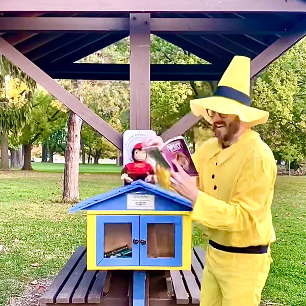 The Man in the Yellow Hat stops to read a book with his friend Curious George.